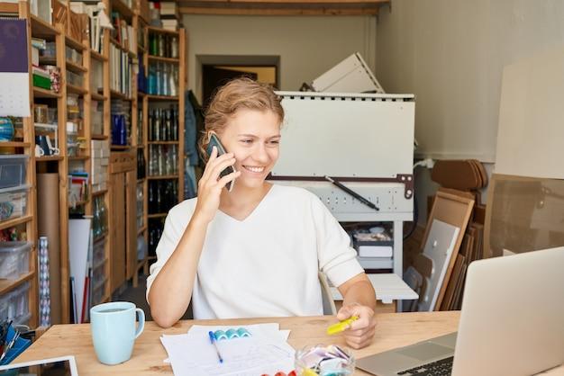 Jovem empresária empresária falando no celular, olhando para o laptop e sorrindo