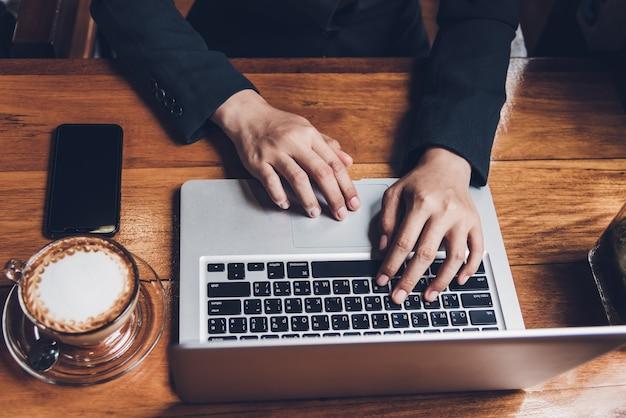 Jovem empresária está trabalhando digitando em seu computador laptop