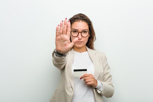 Jovem empresária europeia segurando um cartão de crédito em pé com a mão estendida, mostrando o sinal de stop, impedindo você.