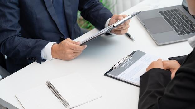 Jovem empresária explicando sobre seu perfil e segurando currículo durante reunião corporativa