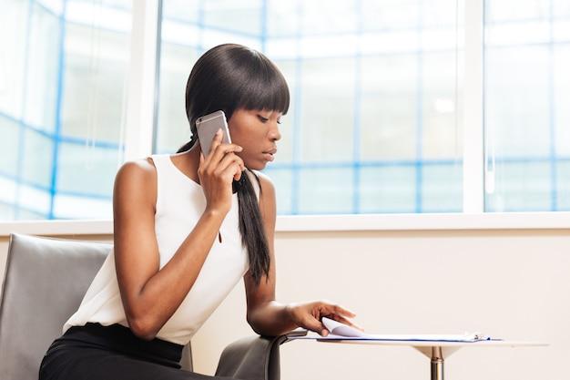 Jovem empresária falando ao telefone e lendo jornal no escritório