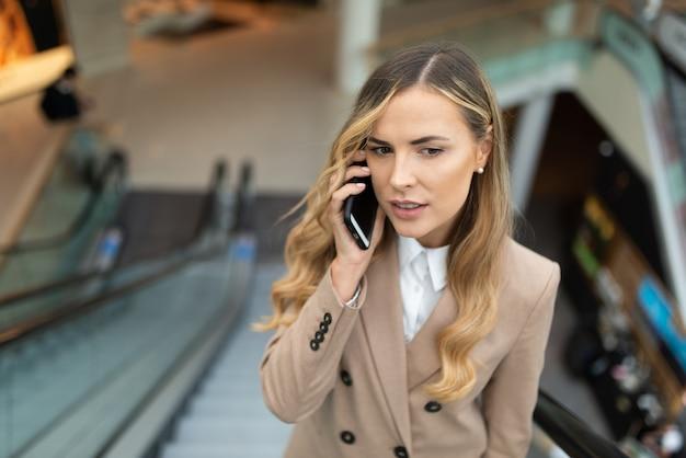 Jovem empresária falando ao telefone em uma escada rolante