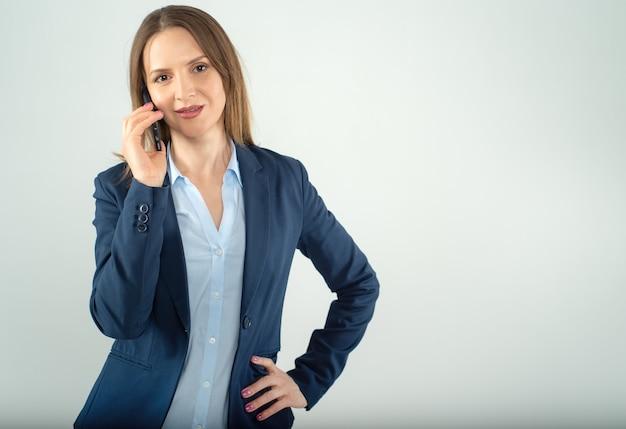 Jovem empresária falando em um telefone celular isolado em um fundo cinza