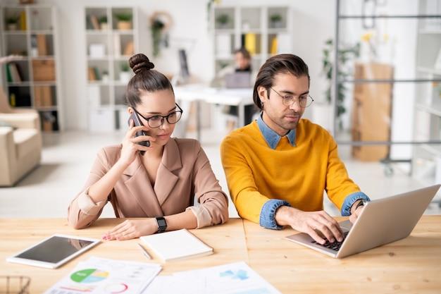 Jovem empresária falando sério com um cliente no smartphone enquanto está sentado ao lado de seu colega de rede na frente do laptop