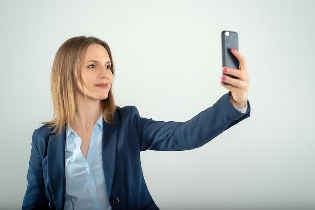 Jovem empresária faz selfie em um telefone celular isolado em fundo cinza