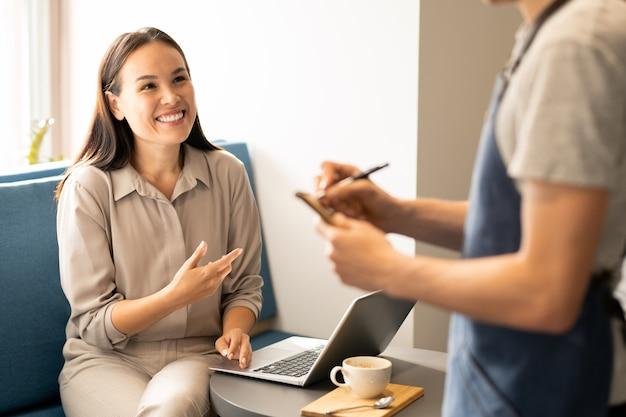 Jovem empresária feliz com laptop olhando para o garçom com um sorriso enquanto faz o pedido no restaurante ou café