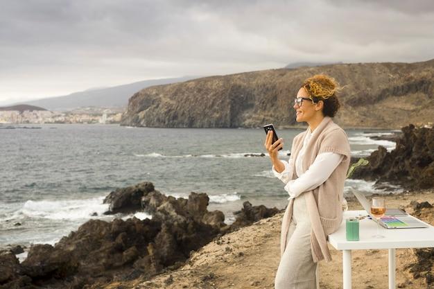 Jovem empresária feliz trabalhando ao ar livre em um escritório alternativo, apreciando a natureza e a brisa do oceano