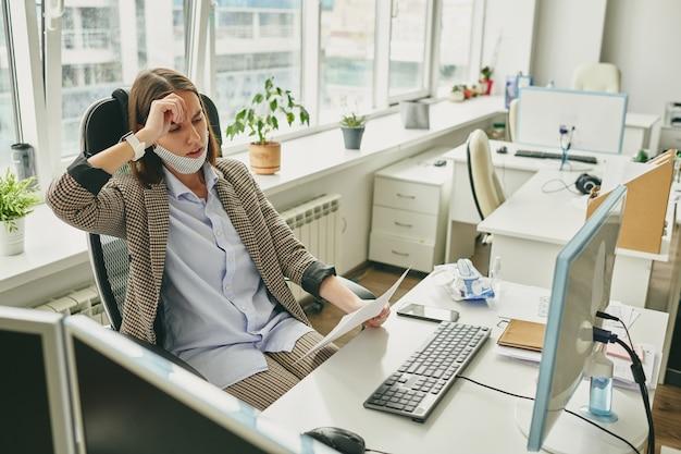 Jovem empresária frustrada estressada com problemas contratuais em um escritório vazio durante o coronavírus