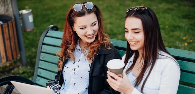 Jovem empresária gorducha de cabelo vermelho sentada no banco com o parceiro tomando um café usando um computador