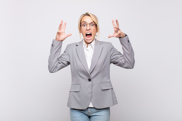 Jovem empresária gritando com as mãos para o alto, furiosa, frustrada, estressada e chateada