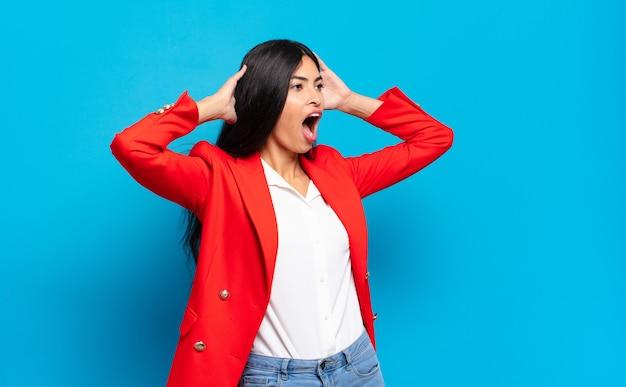 Jovem empresária hispânica com a boca aberta, parecendo horrorizada e chocada por causa de um erro terrível, levando as mãos à cabeça