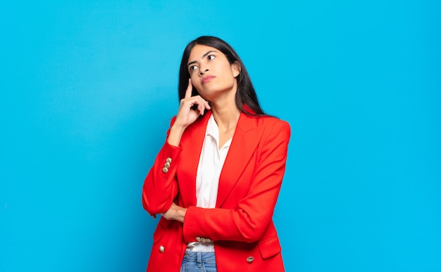 Jovem empresária hispânica com um olhar concentrado, imaginando com uma expressão duvidosa