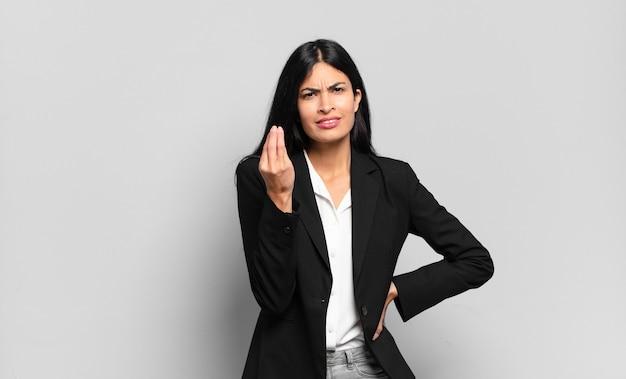Jovem empresária hispânica fazendo capice ou gesto de dinheiro, dizendo para você pagar suas dívidas!