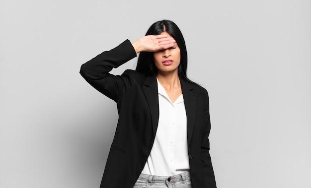 Jovem empresária hispânica parecendo estressada, cansada e frustrada, secando o suor da testa, sentindo-se desesperada e exausta