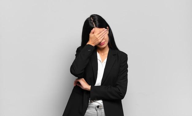 Jovem empresária hispânica parecendo estressada, envergonhada ou chateada, com dor de cabeça, cobrindo o rosto com a mão