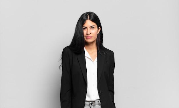 Jovem empresária hispânica parecendo orgulhosa, confiante, descolada, atrevida e arrogante, sorridente, sentindo-se bem-sucedida
