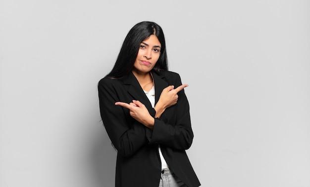 Jovem empresária hispânica parecendo perplexa e confusa, insegura e apontando em direções opostas com dúvidas
