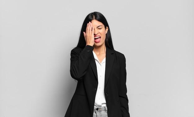 Jovem empresária hispânica parecendo sonolenta, entediada e bocejando, com dor de cabeça e uma das mãos cobrindo metade do rosto