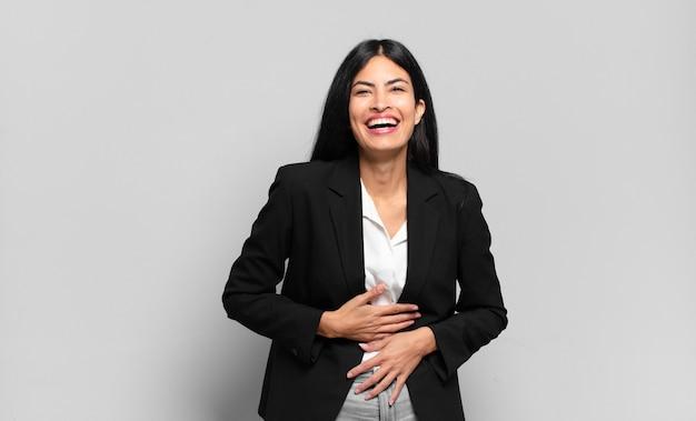 Jovem empresária hispânica rindo alto de uma piada hilária, sentindo-se feliz e alegre, se divertindo