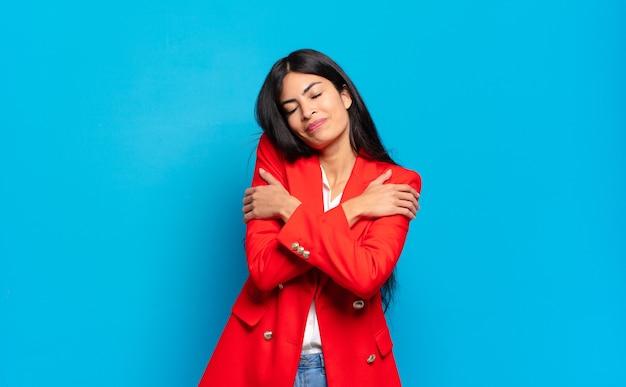 Jovem empresária hispânica se sentindo apaixonada, sorrindo, se acariciando e se abraçando, permanecendo solteira, sendo egoísta e egocêntrica