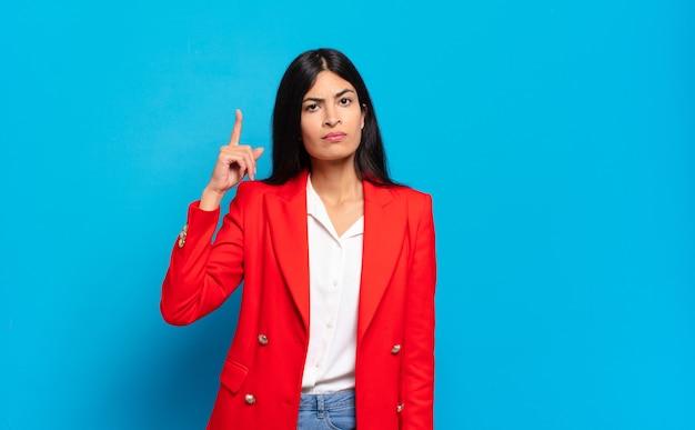 Jovem empresária hispânica se sentindo como um gênio, segurando o dedo com orgulho no ar depois de realizar uma grande ideia, dizendo eureka
