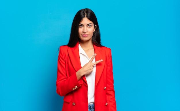 Jovem empresária hispânica se sentindo feliz, positiva e bem-sucedida, com a mão fazendo forma de v no peito, mostrando vitória ou paz