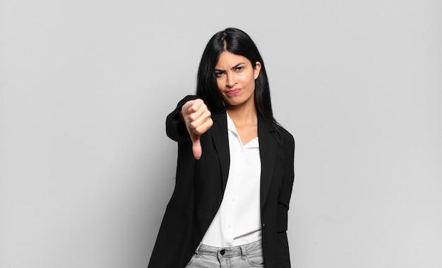 Jovem empresária hispânica se sentindo zangada, irritada, desapontada ou descontente, mostrando o polegar para baixo com um olhar sério
