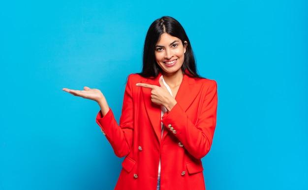 Jovem empresária hispânica sorrindo alegremente e apontando para copiar o espaço na palma da mão ao lado, mostrando ou anunciando um objeto