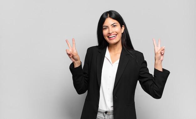 Jovem empresária hispânica sorrindo e parecendo feliz, amigável e satisfeita, gesticulando vitória ou paz com as duas mãos