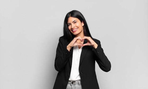 Jovem empresária hispânica sorrindo e se sentindo feliz, romântica e apaixonada