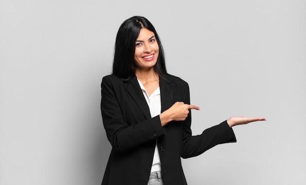 Jovem empresária hispânica sorrindo, sentindo-se feliz, despreocupada e satisfeita, apontando para um conceito ou ideia no espaço da cópia ao lado