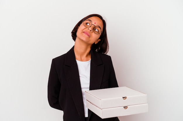 Jovem empresária indiana segurando pizzas isoladas, sonhando em alcançar objetivos e propósitos