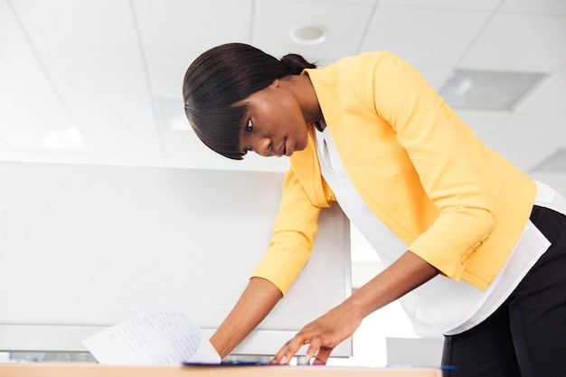 Jovem empresária lendo documento no escritório