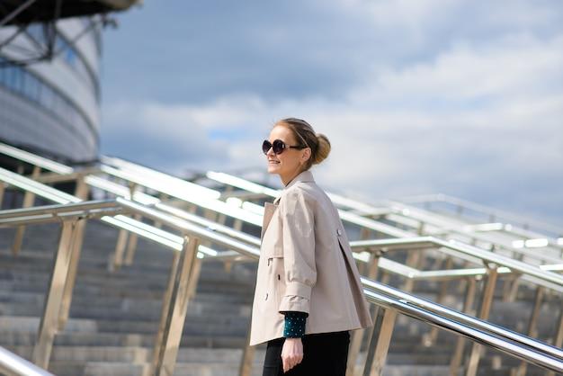 Jovem empresária linda com óculos de sol, telefone, laptop, xícara de café nas ruas da cidade