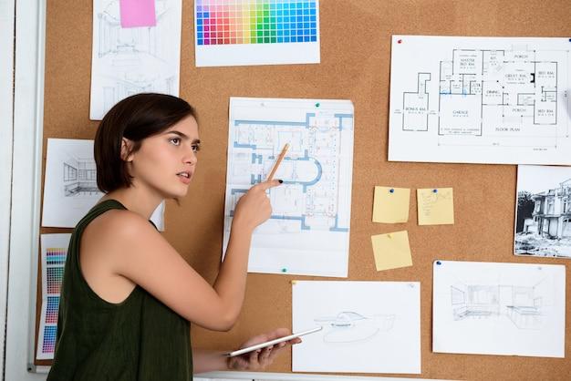 Jovem empresária linda em pé perto da mesa com desenhos