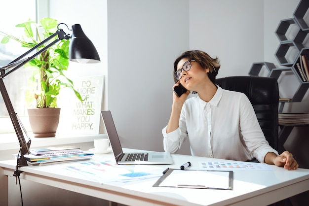 Jovem empresária linda falando no telefone no local de trabalho no escritório.