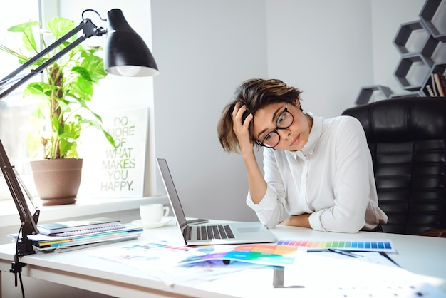 Jovem empresária linda pensando no local de trabalho no escritório.
