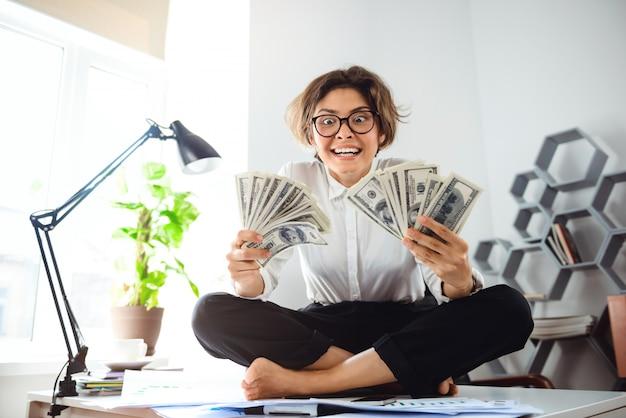 Jovem empresária linda segurando o dinheiro, sentado na mesa no local de trabalho.