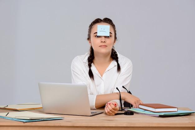 Jovem empresária linda sentada com adesivo na testa no local de trabalho