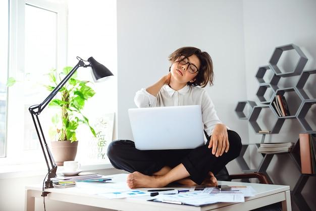 Jovem empresária linda sentada na mesa com o laptop no local de trabalho.