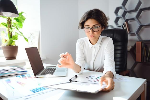 Jovem empresária linda sentada no local de trabalho no escritório.