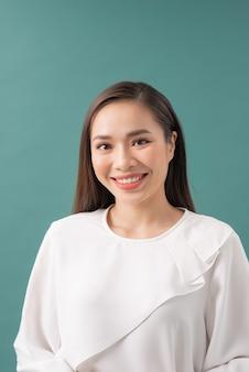 Jovem empresária linda sobre fundo azul, camisa branca, sorrindo e olhando para a câmera