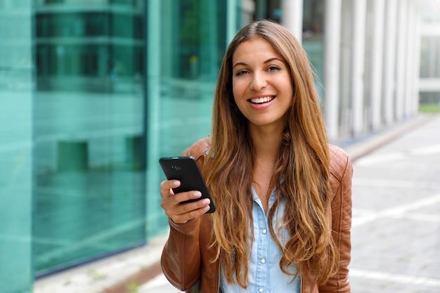 Jovem empresária linda sorrindo e olhando para a câmera, segurando o celular na mão. conceito de negócios.