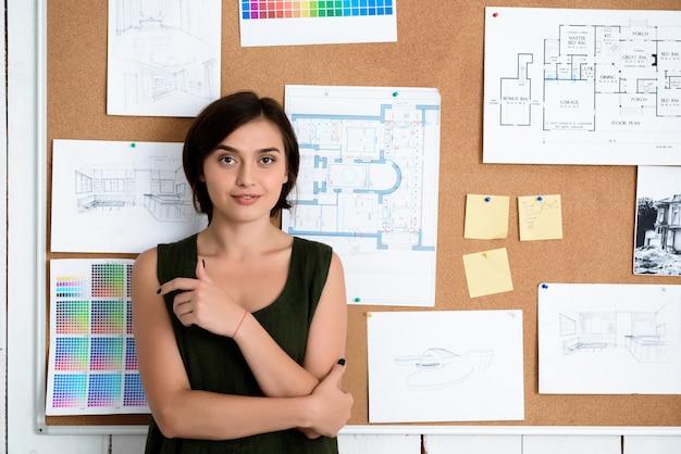 Jovem empresária linda sorrindo, em pé perto da mesa com desenhos