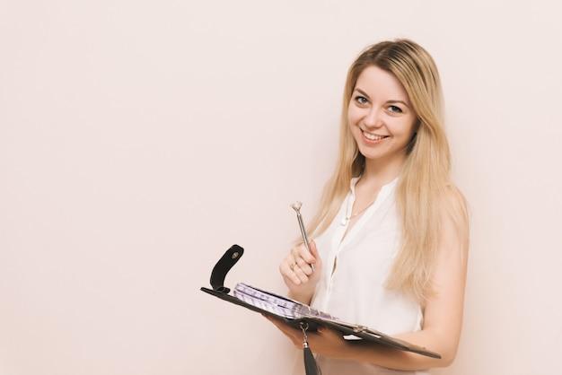 Jovem empresária loira atraente mantém diário de couro preto. retrato de uma bela loira com um notebook