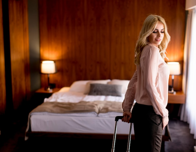Jovem empresária loira chega em um quarto de hotel com mala