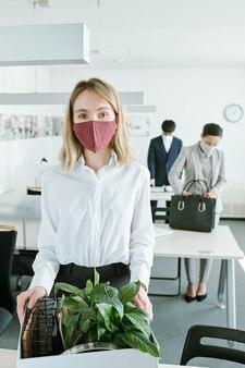 Jovem empresária loira com máscara protetora e roupa formal, colocando a caixa com plantas verdes e material de escritório na mesa dela
