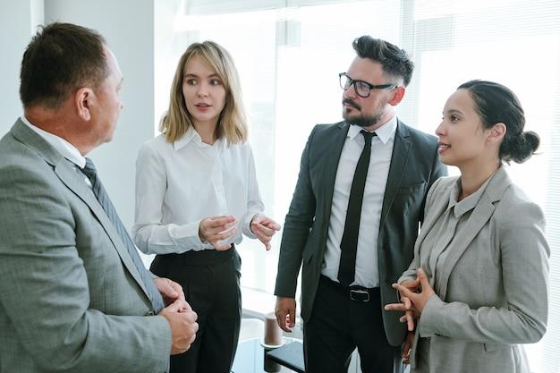Jovem empresária loira compartilhando seus pensamentos sobre um novo projeto de negócios e discutindo-os com colegas na reunião de start-up