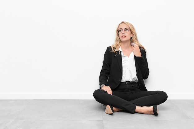 Jovem empresária loira sentada no chão de cimento com um espaço de cópia