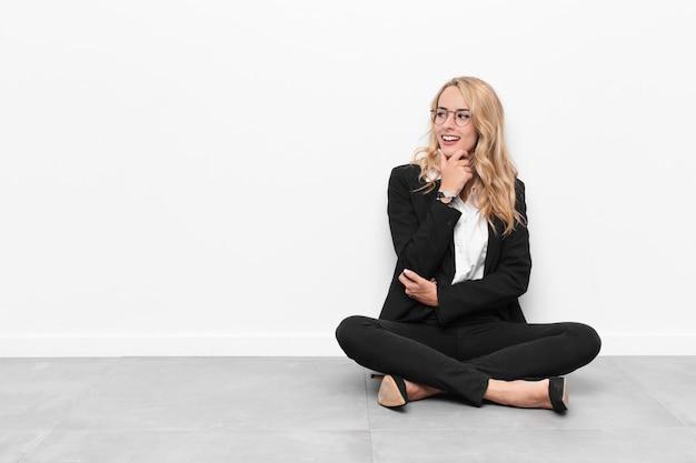Jovem empresária loira sentada no chão de cimento